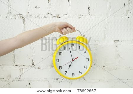 Girl's hand holding yellow alarm clock isolated on white brick backgroung, closeup