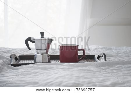 Cup of coffee with kattle on a wooden tray on white bed near window, hotel or home