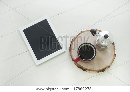 Workspace digital tablet on the table with blank screen on wooden table with cup, top view
