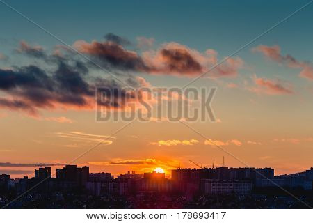Voronezh City in sunset time, Silhouettes of houses in the evening haze and the rays of the setting sun and clouds, evening cityscape