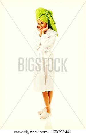 Woman in bathrobe touching face