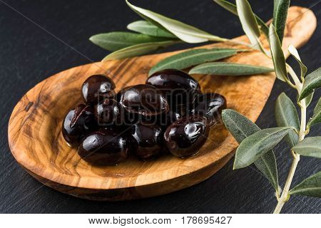 Black olives in wooden spoon and olive branch