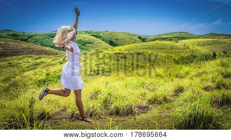 A girl in white dress happy jumping on green grass Hill, Teletubbies Hills, Nusa Penida, Bali, Indonesia.
