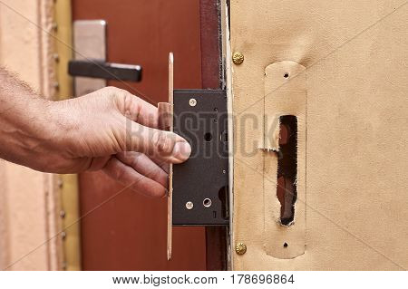 Hand of a locksmith installing a lock in old door close up