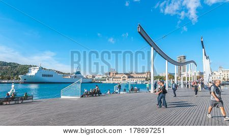 Barcelona, Spain, Nov 3rd, 2013:    Touring Spain - Port Vell waterfront.  Tourists come over the bridge at the marina shopping centre in Barcelona, Spain.  People relax in sunshine on benches while others are on the go.
