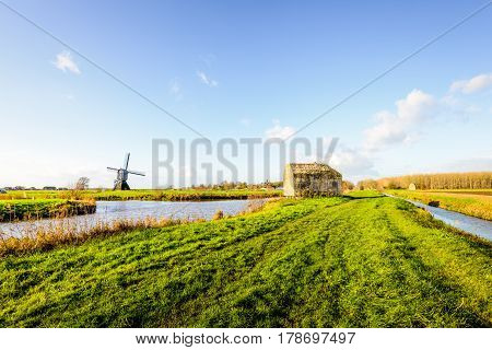 Historic concrete bunker and a wooden hollow post mill together in a Dutch polder landscape on a sunny day in the fall season.