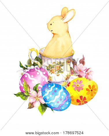 Cute easter bunny in tea cup, with colored eggs and flowers. Watercolor