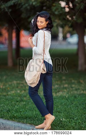 Woman smiling - portrait of happy lovely and beautiful mixed race Asian Caucasian young businesswoman in casual clothes outdoor walking after work in park