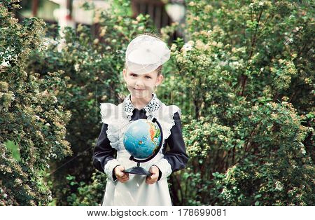 Portrait Of A Beautiful Young First-grader With The Globe With Russian Text. In A Festive School Uni