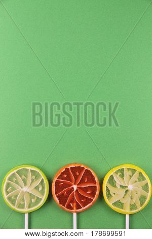 Three citrus lollipops on a green background