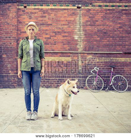Hipster young beautiful girl with vintage road bike in city relaxing with akita inu dog urban scene. Woman commuter cycling on fixed gear bike in town retro city street industrial background.