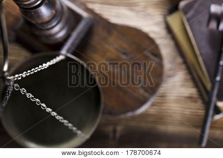 Law and justice concept - gavel of judge and scale of justice and legal code on wooden table. Top view.