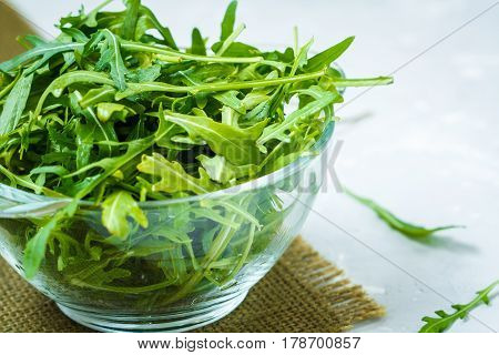 Green raw arugula in a glass bowl.