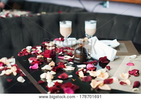romantic place in the cafe. Two cups of coffee on a table strewn with petals. The guy just confessed his love to his girlfriend