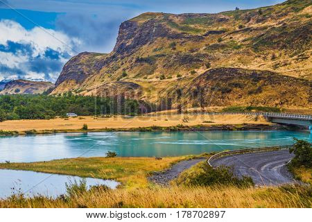Summer in the south of Chile. Rio Paine -  quiet river flow among the picturesque hills of Torres del Paine National Park. Highway and bridge. The concept of extreme and active tourism