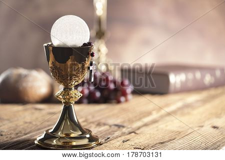 Catholic religion theme. Holy Bible, the cross and gold chalice on wooden table and stone background.