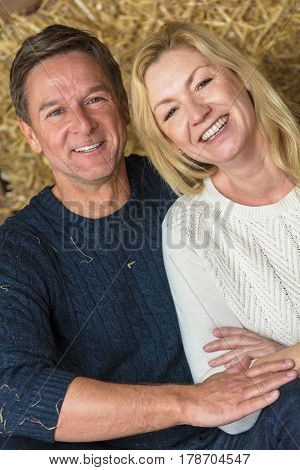 Portrait shot of an attractive, successful and happy middle aged man and woman couple sitting laughing together on hay or straw bales