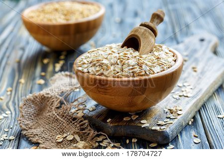 Wooden Scoop In A Bowl With Oat Flaks.
