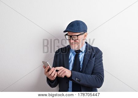 Handsome senior man in blue shirt, jacket, black eyeglasses and flat cap holding smart phone, texting. Studio shot against white wall.