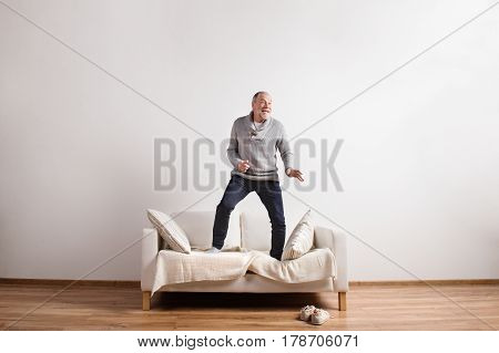 Handsome senior man standing on couch, dancing, having fun. Studio shot against white wall.