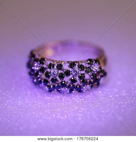 Luxury jewelry ring with jewel gem stone and diamonds in neon lilac glow