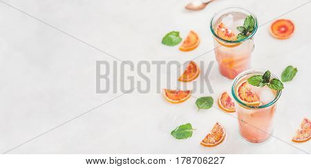 Blood orange fresh summer homemade lemonade with ice and mint in glasses, light grey marble background, selective focus, copy space