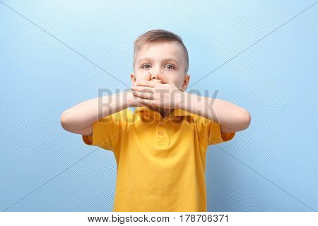 Cute little boy covering mouth with hands, on color background