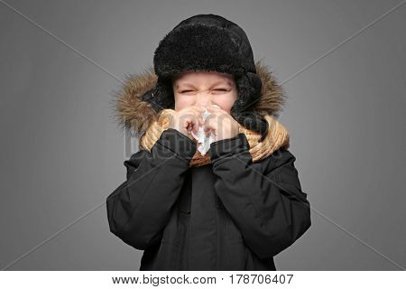 Cute little boy in warm clothes using tissue to blow his nose on gray background