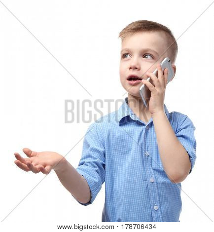 Cute little boy talking by mobile phone on white background
