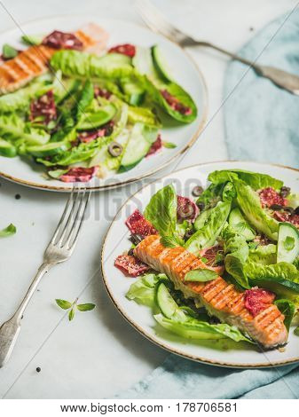 Healthy energy boosting spring salad with grilled salmon, blood orange, olives, cucumber and quinoa over grey marble background, selective focus. Clean eating, dieting, detox, weight loss concept