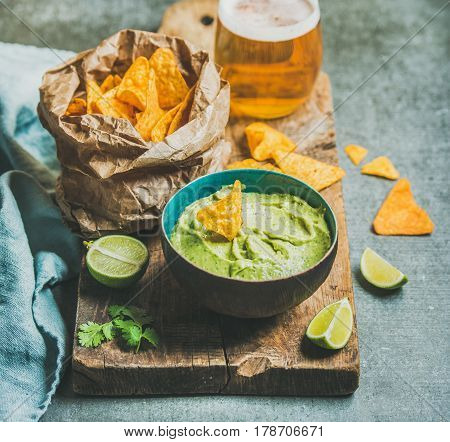 Fresh guacamole sauce in blue ceramic bowl, mexican corn chips, glass of wheat beer on rustic wooden serving board over grey concrete table background, selective focus