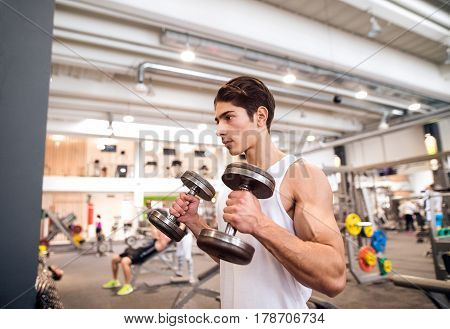 Handsome young hispanic fitness man in gym sitting on bench, working out with weights