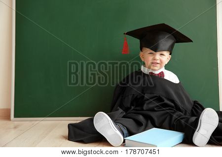 Cute little boy with book, magister hat and gown sitting on floor near blackboard