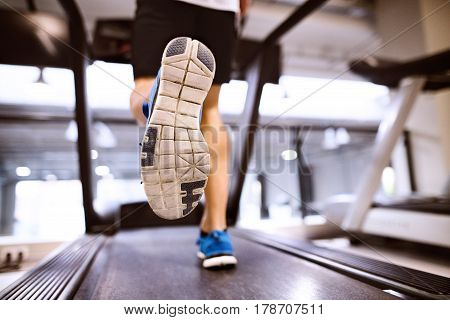 Unrecognizable fitness man in gym doing cardio workout, exercising on treadmill. Close up of sole of his shoe. Sport fitness and healthy lifestyle concept.