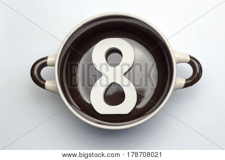 Figure eight at the bottom of the soup tureen on white background.