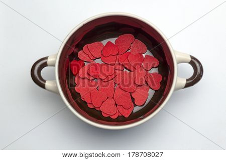 Many red hearts on the bottom of the soup tureen on white background.