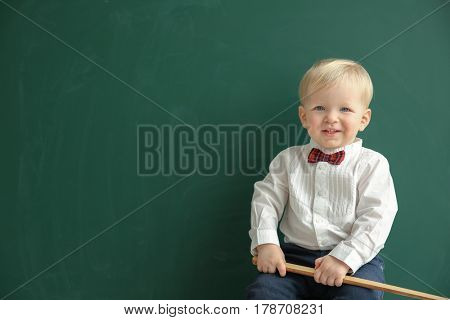 Cute little boy with pointer and blackboard on background
