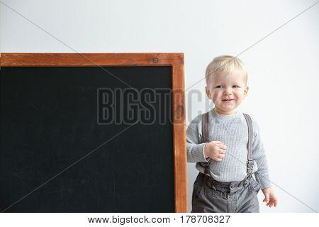 Cute little boy and blackboard on light background