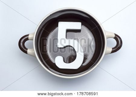 Figure five on the bottom of the soup tureen on white background.