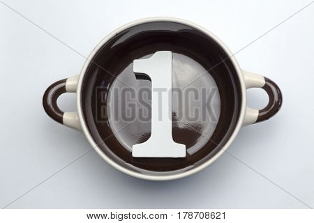 Figure one at the bottom of the soup tureen on white background.