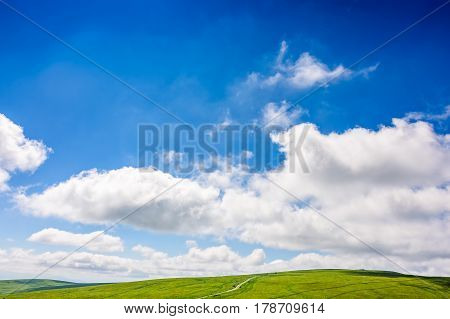 deep blue sky with some clouds over the green and grassy hills of Carpathian alps. road winds uphill the hillside meadow. beautifull minimalistic summer landscape in good day weather.