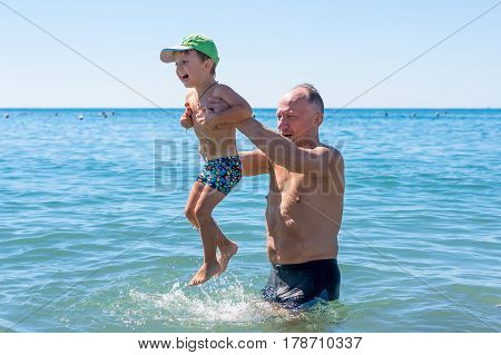 Smiling grandfather and grandson playing at the sea