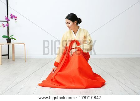 Beautiful young woman in Korean traditional costume sitting on floor