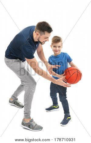 Handsome man and his son playing basketball on white background