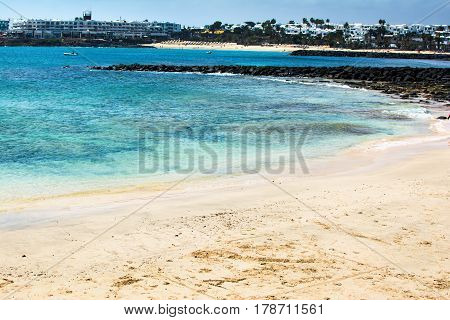 Turquoise waters and yellow sandy coast in Playa Las Cucharas beach in Costa Teguise Lanzarote Canary islands selective focus