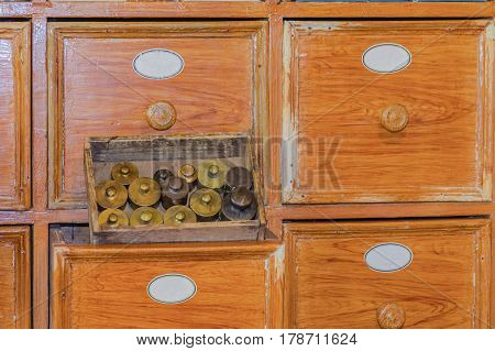 Close up of a very old pharmacy medicine drawer cabinet with small brass weights