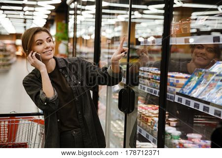Image of cheerful young lady standing in supermarket choosing products while talking by phone. Looking aside.