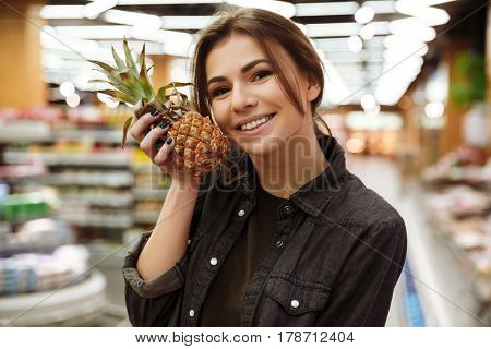Photo of young happy woman in supermarket choosing fruits and holding pineapple. Looking at camera.