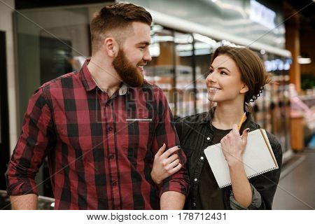 Image of young smiling loving couple in supermarket choosing products. Looking at each other.