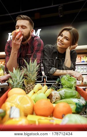 Photo of happy young loving couple in supermarket with shopping trolley choosing fruits. Woman looking at camera.